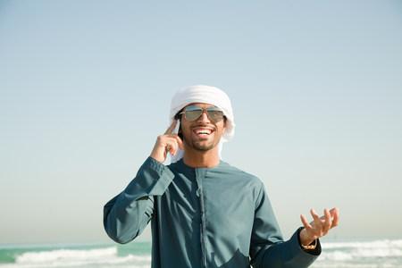 Middle Eastern man using mobile phone on the beach 版權商用圖片