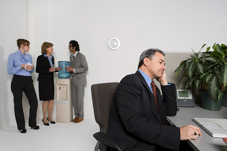 Businessman at desk with others gossiping by water cooler