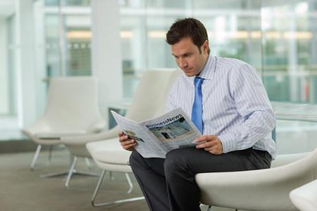 Businessman reading magazine Banque d'images