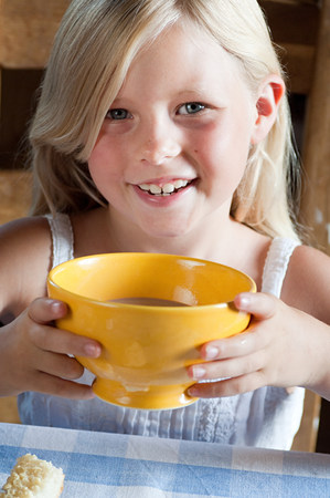 Girl with hot drink in bowl Imagens