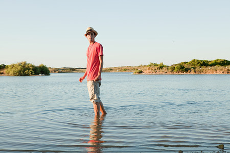 Teenage boy standing in lake