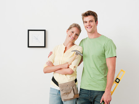 Young couple with tools picture on wall