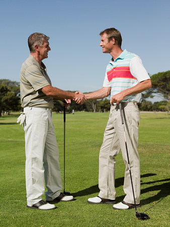 Two mature men shaking hands on golf course