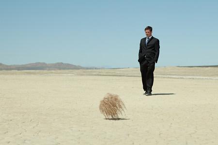 Geschäftsmann in der Wüste mit Tumbleweed Standard-Bild