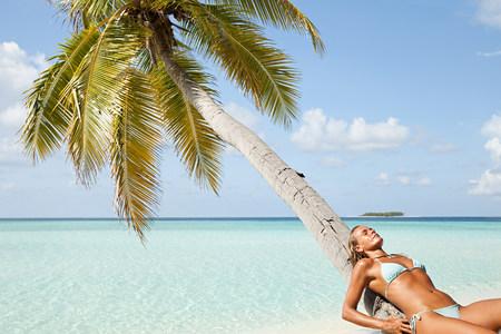 Woman leaning on palm tree, Maadaugalla Island, North Huvadhu Atoll, Maldives