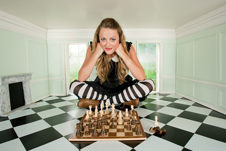 Young woman in small room with chess set Imagens