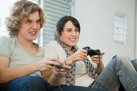 Teenage couple playing with games consoles
