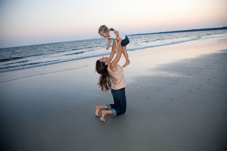 Mother lifting daughter on beach 版權商用圖片
