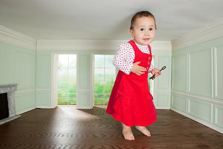 Großes Kleinkindmädchen in einem winzigen Zimmer mit einem Schlüssel