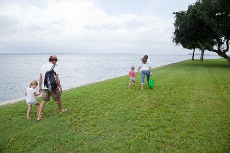 Family walking along grass by the sea