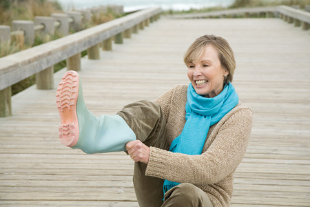 Woman putting on rubber boots