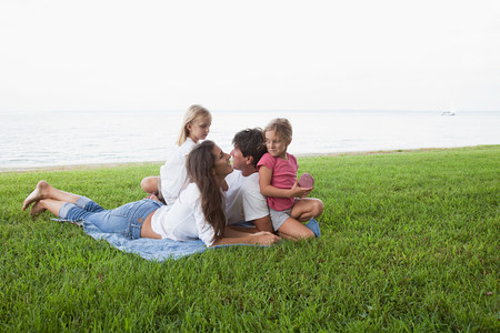 Family relaxing on grass by the sea 스톡 콘텐츠