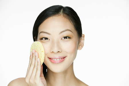 Young woman using sponge on face