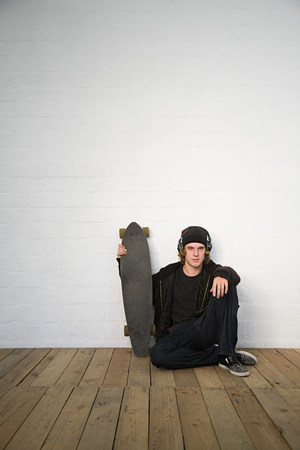 Portrait of teenage boy sitting on floor with skateboard Stock Photo