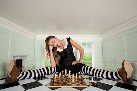 Young woman in small room with chess set 스톡 콘텐츠