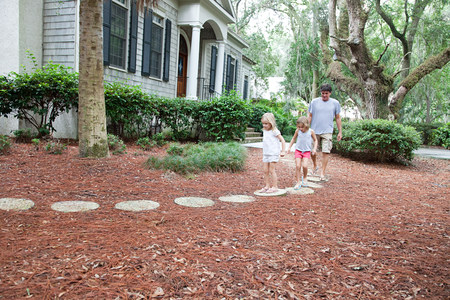 Father and daughters walking on garden path