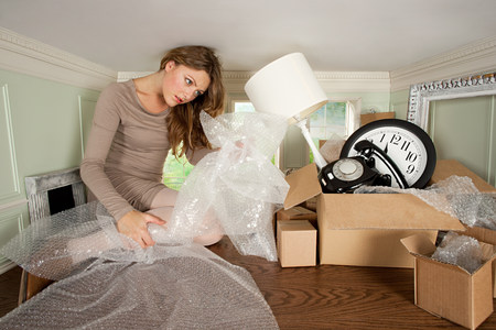 Young woman packing box of objects in small room