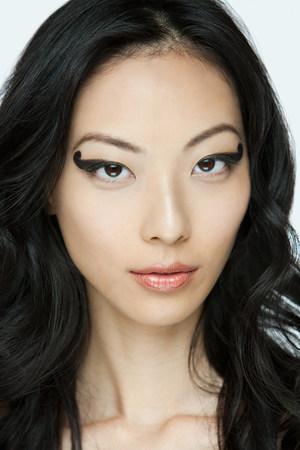 Young woman with black eye makeup Фото со стока