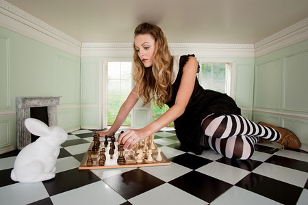 Young woman playing chess with rabbit 스톡 콘텐츠