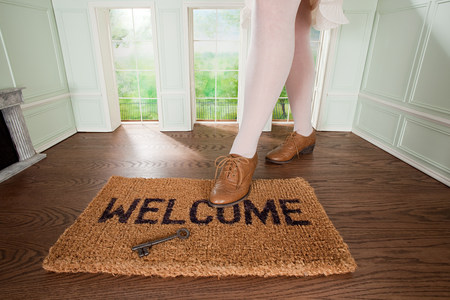 Legs of a woman and welcome mat with key in small room