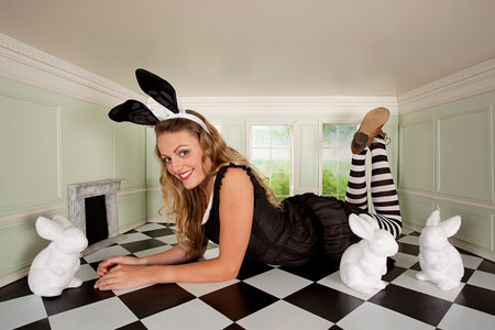 Young woman in small room with bunny ears and rabbit figures