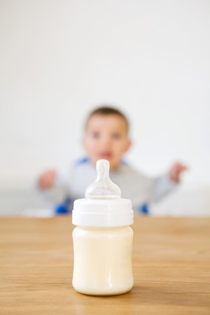 Baby bottle in foreground and baby in background