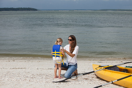 Mother putting life jacket on daughter for kayaking