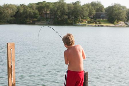 Boy fishing in lake Imagens