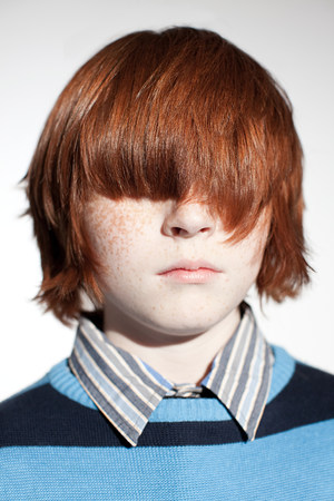 Boy with hair covering his eyes Imagens