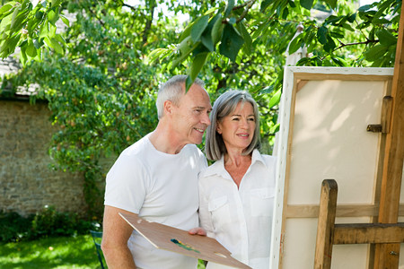 Mature couple, woman painting at easel 版權商用圖片