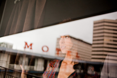 Young woman in motel window Imagens