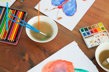 Children's paintbrushes and paintings on table Standard-Bild - 116722877