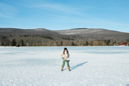 Girl standing in snow with ice skates Stock Photo
