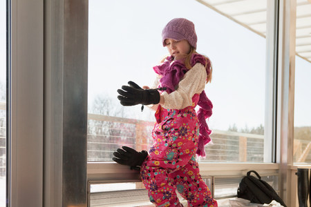 Girl getting dressed in winter clothing Stock Photo