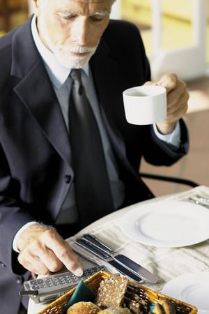 Businessman having breakfast with cellphone