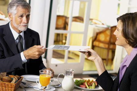Businessman and businesswoman conducting business over breakfast