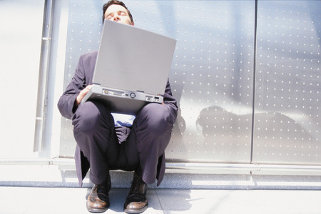 Businessman with computer sitting in the sun Stock Photo