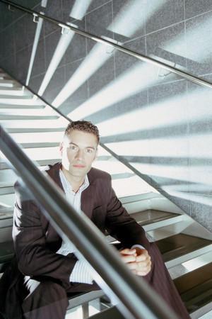 Businessman sitting on modern stairway