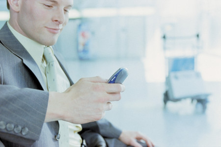 Businessman with cellphone at airport Stock Photo