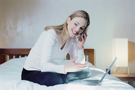 Woman in bedroom with laptop Stock Photo
