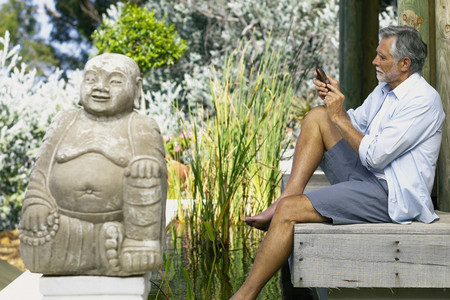 Man beside pool and buddha with cellphone
