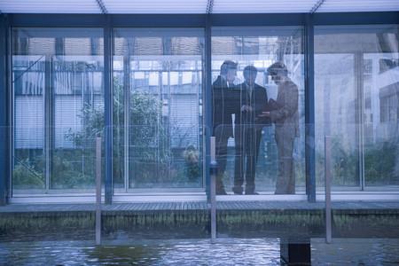 Businessmen in glass walkway 스톡 콘텐츠