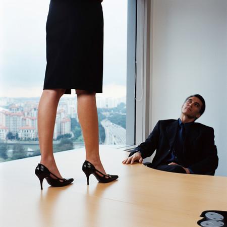 Businessman watching woman on desk 写真素材