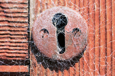 A keyhole covered in cobwebs Stock Photo