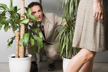 Man hiding in plants and watching woman 写真素材 - 116727807