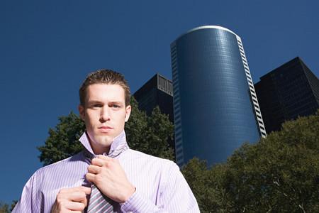 Male office worker adjusting necktie