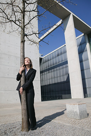 Businesswoman hugging a tree