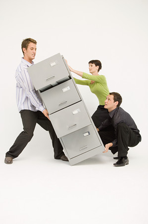 Three office workers lifting heavy filing cabinet
