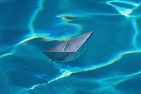 A paper boat on a swimming pool
