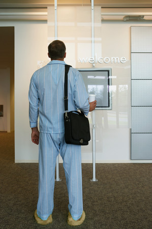 Businessman arriving at work in pajamas 写真素材